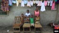Victoria Topay dan anak-anaknya berpose di West Point, Monrovia (foto: dok). Kursi kosong menggambarkan anggota keluarga yang tewas akibat ebola, termasuk suami Victoria.