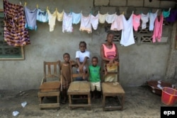 Victoria Topay and her children pose for a family portrait at her home in West Point, Monrovia, Liberia. The empty chairs are a symbolic representation of Victoria's late husband and family members who died of the Ebola virus, March 24, 2016.