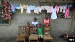 Une famille pose à West Point au Liberia. Les chaises vides représentent le chef de famille et les autres membres de famille emportés par Ebola. EPA/AHMED JALLANZO