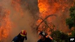 آتشنشانان در حال مبارزه با آتشسوزی جنگلی در روستایی در جزیره ائوبویا در ۱۷۶ کیلومتری شمال آتن، یونان - ۱۸ مرداد ۱۴۰۰