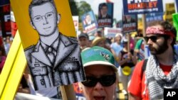 Protesters march during a rally in support of Army Pfc. Bradley Manning, whose court-martial begins Monday for the largest leak of classified documents in U.S. history, outside of Fort Meade, Maryland, June 1, 2013.