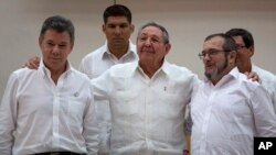 FILE - Cuba's President Raul Castro, center, stands with Colombian President Juan Manuel Santos, left, and Commander the Revolutionary Armed Forces of Colombia or FARC, Timoleon Jimenez, in Havana, Cuba, Sept. 23, 2015.
