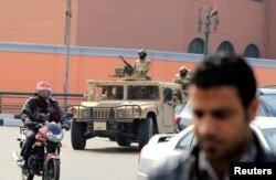 Army soldiers in military vehicles move to take up positions during the fourth anniversary of the 2011 uprising that toppled Hosni Mubarak in Cairo, Jan. 25, 2015.