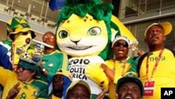 FILE: Bafana Bafana fans, accompanied by World Cup 2010 mascot, Zakumi, gather to welcome their team at the O.R. Tambo international airport near Johannesburg.