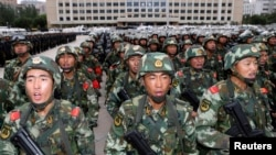 Armed paramilitary policemen stand in formation during a gathering to mobilize security operations in Urumqi, Xinjiang Uighur Autonomous Region, June 29, 2013.