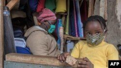 FILE - A woman who trades in fabrics, and her child, wears face masks as preventive measure against the COVID-19 coronavirus, in her shop inside Lilongwe City market in Lilongwe on May 18, 2020.