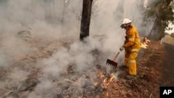 A firefighter uses a rake to move burning debris as he battles a fire near Burrill Lake, Australia, Sunday, Jan. 5, 2020. (AP Photo/Rick Rycroft)