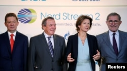 Gazprom chief Alexei Miller, from left, poses with former German Chancellor Gerhard Schroeder, Isabelle Kocher, chief executive officer of French gas and power group Engie, and Gerard Mestrallet, Engie's former chairman & CEO, now non-executive chairman, in Paris, April 24, 2017, after western partners of gas giant Gazprom agreed on financing the 9.5-billion euro ($10.32 billion) Nord Stream 2 pipeline.