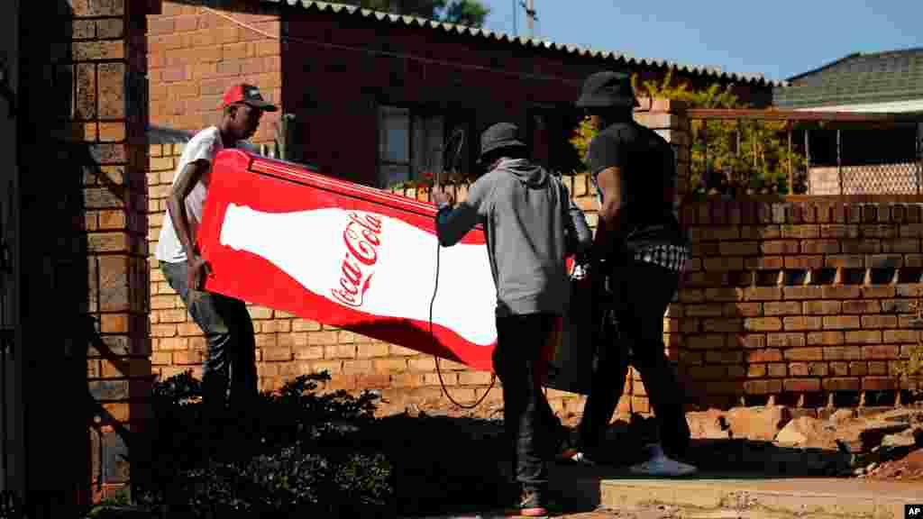 Des manifestants transportent un réfrigérateur Coca Cola qu'ils ont pillé dans un magasin, lors des manifestations à Atteridgeville, en Afrique du Sud, le 21 juin 2016.