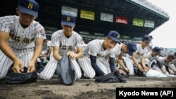 FILE - Akashi Commercial High School baseball players collect dirt of the grounds after being defeated by Riseisha High School during a semifinal game at the National High School Baseball Championship at Koshien Stadium in Nishinomiya on Aug. 20, 2019. (Kyodo News via AP)