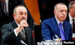 FILE - Turkish President Recep Tayyip Erdogan and Turkish Foreign Minister Mevlut Cavusoglu attend the Libya summit in Berlin, Germany, Jan. 19, 2020.