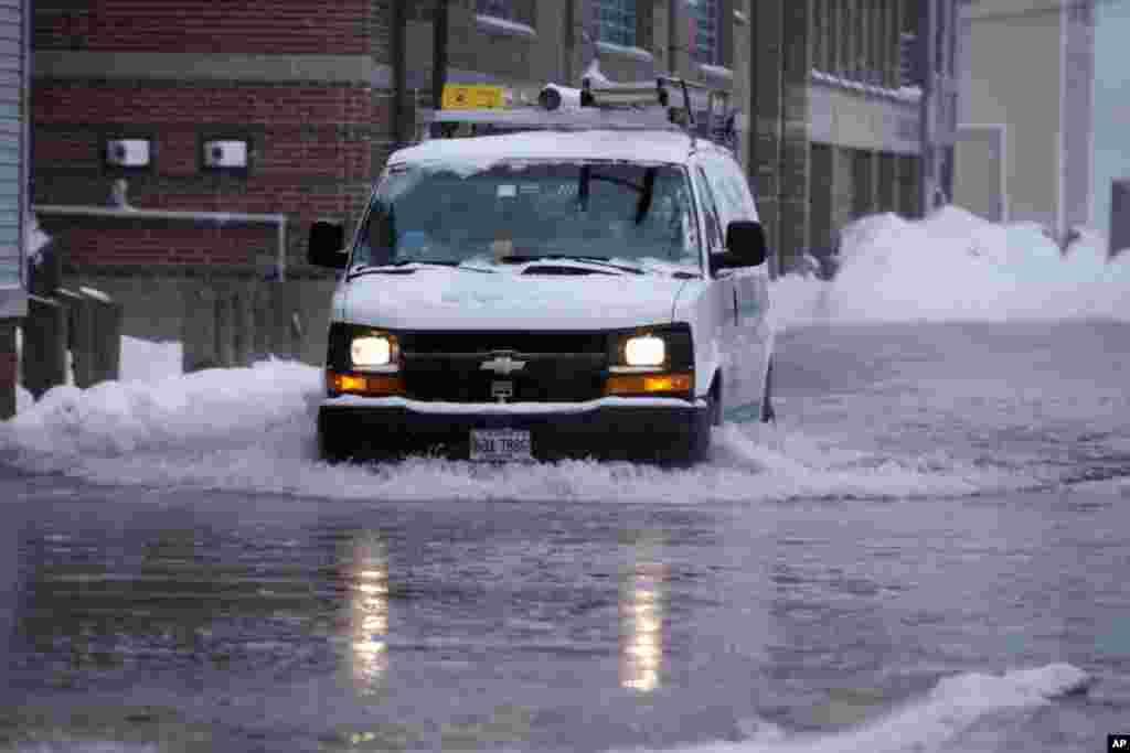 Sebuah truk melintasi banjir yang menggenangi sebuah jalan di Portland, negara bagian Maine, Kamis (2/1).(AP/Robert F. Bukaty)