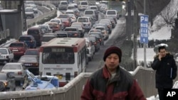 Chinese walk on a pedestrian overhead bridge next to the vehicles driven in heavy traffic in Beijing (File)
