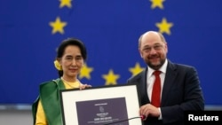 Burma's pro-democracy leader Aung San Suu Kyi (L) holds her 1990 Sakharov Prize, besides European Parliament President Martin Schulz, during an award ceremony in Strasbourg, France, Oct. 22, 2013.