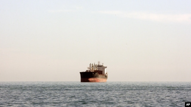 A cargo ship is seen between the Iranian city port of Bandar Abbas and Qeshm Island in the strategic waterway the Persian Gulf.