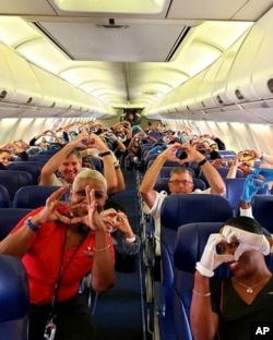 This Friday, March 27, 2020, photo provided by Southwest Airlines employee Dayartra Etheridge shows health care workers, other passengers and flight crew aboard a Southwest flight from Atlanta to New York's LaGuardia Airport.