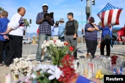 Mourners gather around a makeshift memorial in honor of victims following Wednesday's attack in San Bernardino, California December 5, 2015.