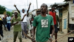FILE - Demonstrators, some carrying machetes and stones, shout as police dismantle a barricade in the Kanyosha district of Bujumbura, Burundi, May 6, 2015.