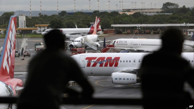 FILE - People look at jetliners at the Brasilia international airport, in Brasilia, Brazil, Nov. 28, 2013