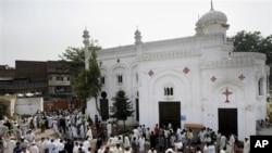 Orang-orang berkumpul di depan sebuah gereja di Peshawar, Pakistan, pasca serangan bom bunuh diri (22/9).