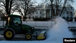 Seorang petugas membersihkan jalanan di depan Gedung Putih yang dipenuhi salju.
