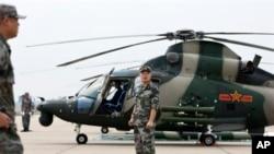 中国士兵守卫在一架武直-9旁边。(2012资料照)