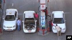 Para pengemudi taksi berbincang sambil mengisi bensin di sebuah pom bensin di Kairo (foto: ilustrasi).