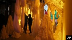 This Nov. 2, 2018 photo shows Kareem Rahma, right, founder and CEO of the Nameless Network and co-creator of The Museum of Pizza appears in an art installation in New York. (AP Photo/Bebeto Matthews)