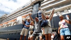 Passengers react after they disembark from the MS Westerdam, back, at the port of Sihanoukville, Cambodia, Friday, Feb. 14, 2020. Hundreds of cruise ship passengers long stranded at sea by virus fears cheered as they finally disembarked Friday and were welcomed to Cambodia. (AP P