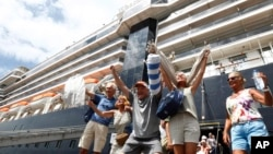 Passengers react after they disembark from the MS Westerdam, back, at the port of Sihanoukville, Cambodia, Friday, Feb. 14, 2020. Hundreds of cruise ship passengers long stranded at sea by virus fears cheered as they finally disembarked Friday and were welcomed to Cambodia.