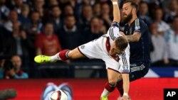 Le capitaine de l'équipe de l'Allemagne, Bastian Schweinsteiger, à gauche, dans l'action avec Steven Fletcher d'Ecosse, à droite, au cours de leur match de qualification de football à Hampden Park, Glasgow, Écosse, le lundi 7 septembre 2015.