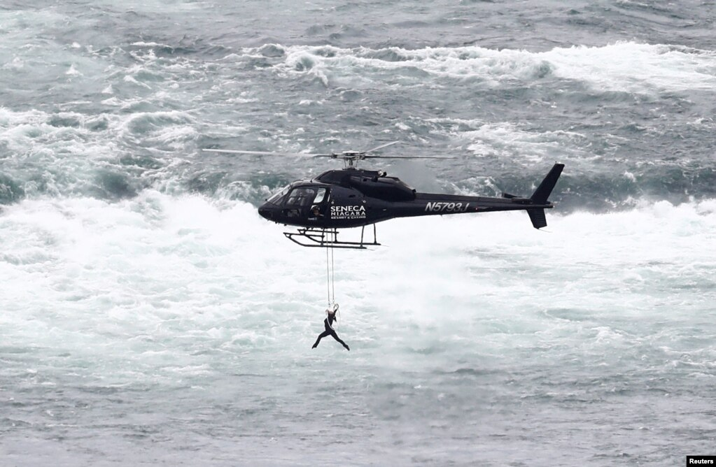 Perempuan seniman akrobatik Erendira Wallenda menggigit tali yang tergantung di helikopter yang terbang di atas air terjun Niagara dalam atraksi di Niagara Falls, New York.