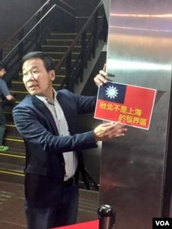 国民党籍台北市议员钟小平向媒体展示抗议标语。他指责柯文哲市长身份款待沙海林是自我矮化。(美国之音林枫拍摄)