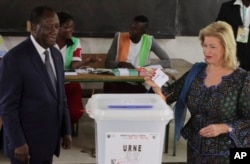 FILE - Ivory Coast's President Alassane Ouattara, left, and his wife, Dominique Ouattara, cast their ballots during the Ivory Coast referendum in Abidjan, Ivory Coast, Oct. 30, 2016.