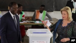 FILE - Ivory Coast's President Alassane Ouattara, left, and his wife, Dominique Ouattara, cast their ballots during the Ivory Cost referendum in Abidjan, Ivory Coast, Oct. 30, 2016.