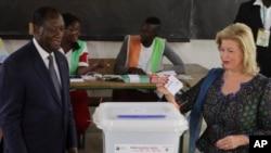 Le président de la Côte d'Ivoire, Alassane Ouattara, et son épouse, Dominique Ouattara, ont voté lors du référendum à Abidjan, en Côte d'Ivoire, 30 octobre 2016.