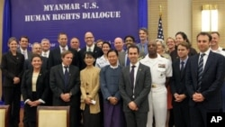 Myanmar opposition leader Aung San Suu Kyi, foreground third from left, and attendees pose for photos during the Myanmar-US Human Rights Dialogue in Naypyitaw, Myanmar, Wednesday, Oct. 17, 2012. (AP Photo/Khin Maung Win)