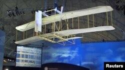 Una réplica de la aeronave de los hermanos Wright planea encima de la audiencia durante la ceremonia por el 100 aniversario del primer vuelo celebrado en el centro Steven F. Udvar-Hazy del Museo del Aire y del Espacio del Smithsonian.
