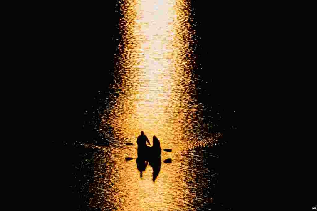 Sepasang muda-mudi mengayuh perahu kano di sungai Potomac, sambil menikmati matahari terbenam di Washington DC.