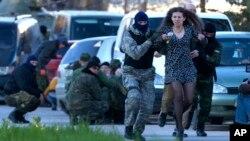Milicianos pro-rusos evacúan a una residente durante el asalto de tropas rusas a la base de Belbek, en Crimea.