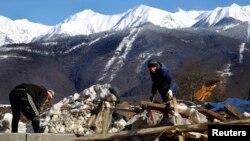 Рабочие убирают строительный мусор у строящейся гостиницы в окрестностях города Сочи. Россия. 2 февраля 2014 г.