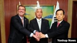 싱가포르에서 열린 제14차 아시아안보회의에 참석 중인 한민구 국방부 장관 (오른쪽)이 30일 애슈터 카터 미국 국방장관, 나카타니 겐 일본 방위상과 회담에 앞서 악수하고 있다.