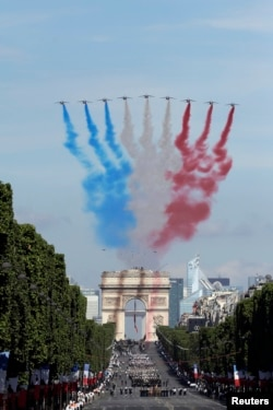 French Alphajets of the Patrouille de France fly over the Champs Elysees avenue, with the Arc de Triomphe in background, during the Bastille Day parade in Paris, July 14, 2017.