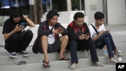 "People look at their smartphones as they play ""Pokemon Go"" in Jakarta, Indonesia. Indonesian authorities banned the playing of ""Pokemon Go"" from the presidential palace on Wednesday, July 20, 2016. (AP Photo/Tatan Syuflana)"