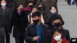 People wear face mask amid the concern over the spread of the coronavirus in Pyongyang, North Korea, Wednesday, April, 1, 2020.