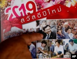 In this March 14, 2019, photo, Nuwate Jiamwong, the 59-year-old farmer, points at an image of former Prime Minister Thaksin Shinawatra on a calendar in Nakhon Ratchasima, Thailand.