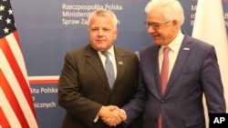 U.S. deputy secretary of state, John Sullivan, right, shakes hands with Polish Foreign Minister Jacek Czaputowicz in Warsaw, Poland, Wednesday, Dec. 19, 2018.