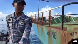 FILE - Indonesian navy personnel stand guard on an Indonesian navy ship anchored next to illegal fishing vessel Viking which was seized by Indonesia's Navy before its sinking in the waters off Pangandaran, West Java, Indonesia, March 14, 2016.