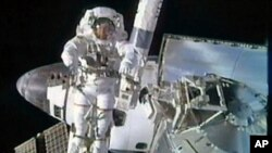 Spacewalker Bowen moves into position aboard the International Space Station's robotic arm as he works outside the station in this image from NASA TV, February 28, 2011