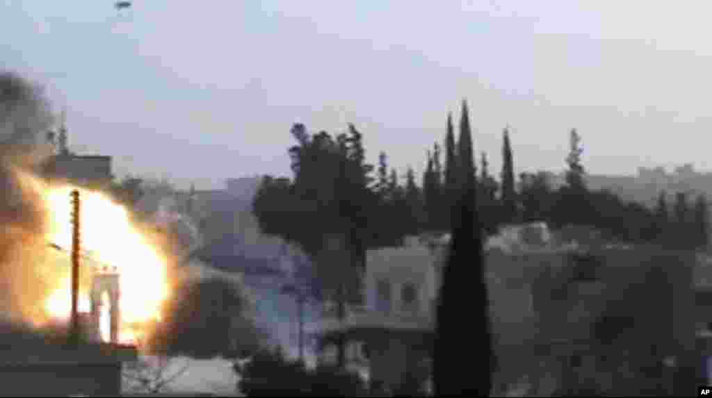 This image from amateur video released by Syrian Media Centre purports to show an explosion as a tank fires a shell in Idlib, Syria, March 13, 2012. (AP/Syrian Media Centre)